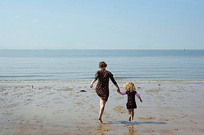 Mother and daughter walking on beach - p42919039f by Mischa Keijser