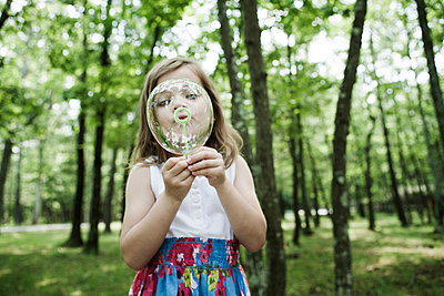 Girl blowing bubbles in forest - p924m711199f by Bill Miles