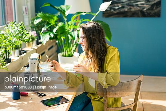 Fashion designer sitting at desk in her studio using smartphone - p300m1581659 by Robijn Page