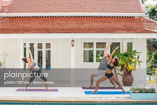Two women and a man practicing yoga on terrace - p300m1587444 von Mosu Media