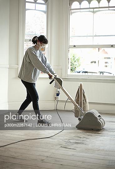 Woman using floor sander on floorboards in empty living room, London, United Kingdom - p300m2287142 von LOUIS CHRISTIAN
