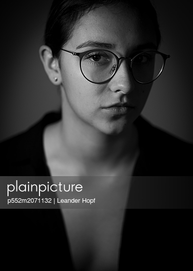 Young woman wearing glasses - p552m2071132 by Leander Hopf