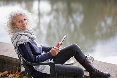 Portrait confident active senior woman using digital tablet at park pond - p1023m2187629 by Tom Merton