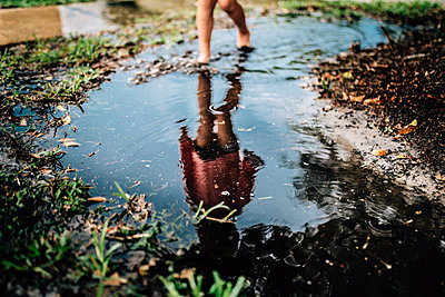 Low section of girl standing in puddle - p1166m1507799 by Cavan Images