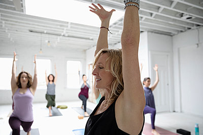 Smiling woman practicing yoga warrior one pose in yoga class - p1192m1583396 by Hero Images
