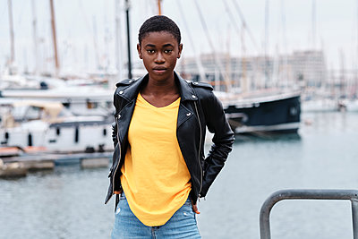 Young woman wearing jacket staring while standing with hands in pockets at harbor - p300m2250172 by Alvaro Gonzalez