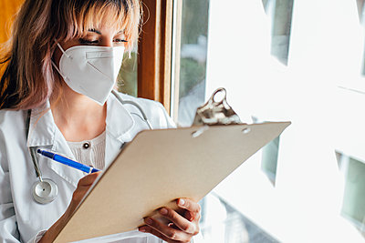 Female doctor wearing protective face mask writing on clipboard in clinic - p300m2290493 by Elena Helade