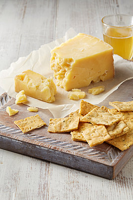Still life with cheddar cheese and crackers on cutting board - p429m2068687 by Danielle Wood