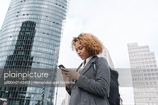 Woman using smartphone with office buildings in background, Berlin, Germany - p300m2143453 by Hernandez and Sorokina