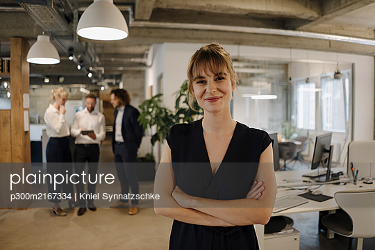 Portrait of confident businesswoman in office with colleagues in background - p300m2167334 von Kniel Synnatzschke