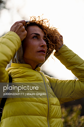 Mid adult sportswoman wearing hood while standing at park - p300m2243111 by Mauro Grigollo