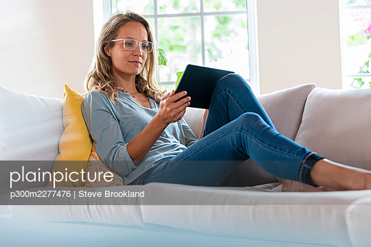 Woman with eyeglasses using digital tablet while sitting on sofa at home - p300m2277476 by Steve Brookland