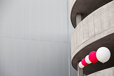 Red and white balloons floating in circular cement parking lot. - p1328m1486849 by Pierre Desrosiers