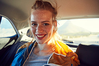 Smiling young woman on the back seat of a car - p300m1460711 by Martina Ferrari