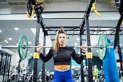 Woman lifting barbell in gym - p300m2167401 von Oscar Carrascosa Martinez