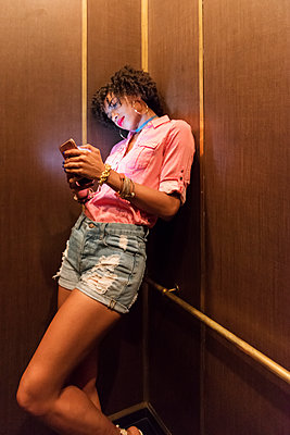 Stylish woman using cell phone in elevator - p312m1533481 by Karl Forsberg