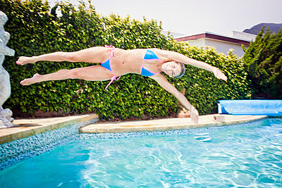 Woman jumping into a pool - p930m814921 by Ignatio Bravo