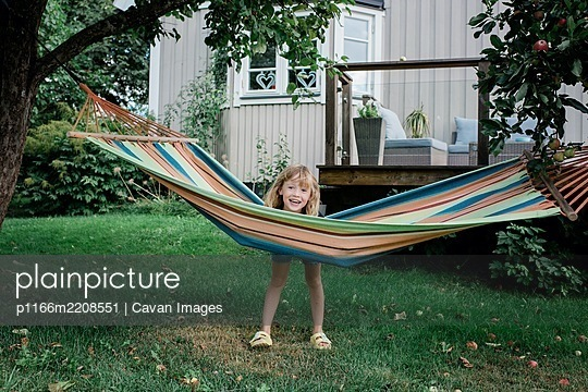 young girl standing by a hammock smiling have fun in a garden at home - p1166m2208551 by Cavan Images