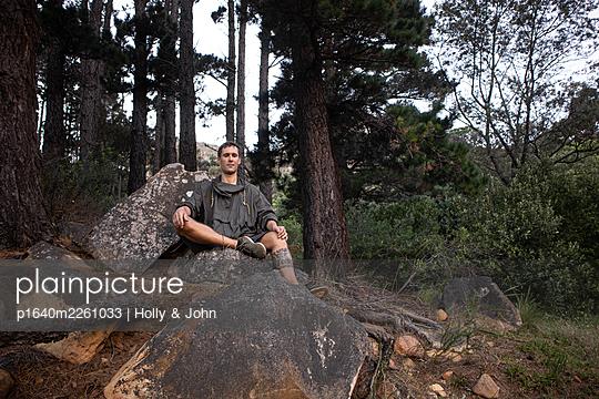 Wanderer mit Gebetskette sitzt auf einem Felsblock - p1640m2261033 von Holly & John
