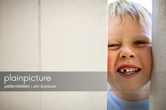 Portrait of small boy making a funny face and showing his missing tooth as he looks through partly open door.  - p456m669684 by Jim Erickson
