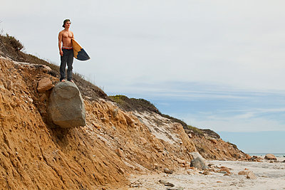 Man with surfboard standing on rocky mountain against sky - p1166m985491f by Cavan Images