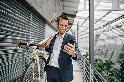 Smiling businessman with cell phone carrying bicycle in modern office building - p300m2155442 by Joseffson
