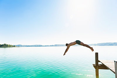 Young man in swimming shorts jumping from jetty into lake - p300m2197738 by Daniel Ingold