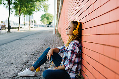 Woman listening music with eyes closed while sitting on footpath against brick wall - p300m2227373 by Xavier Lorenzo