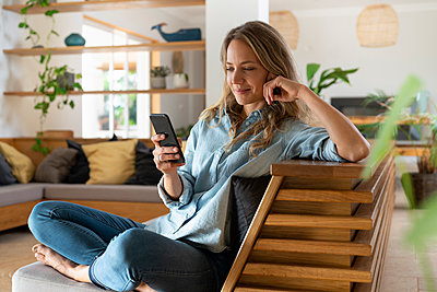 Blond hair woman text messaging through smart phone while sitting in living room - p300m2277556 by Steve Brookland