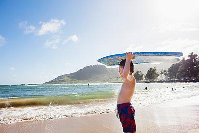 Boy with board on beach - p312m1147541 by Plattform photography