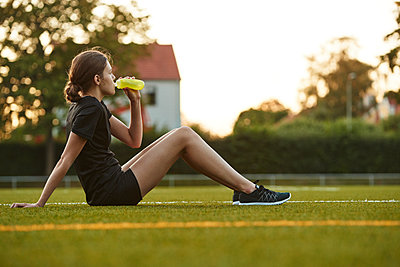 Teenage girl drinking from bottle in playing field - p312m1442849 by Johan Alp