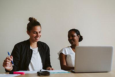Smiling women talking in office - p312m2146310 by Stina Gränfors