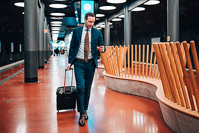 Full length of businessman with luggage and mobile phone walking in railroad platform - p426m1580133 by Maskot