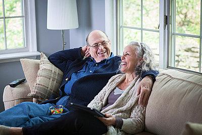 Senior couple using digital laptop on sofa at home - p924m664950f by Steve Prezant