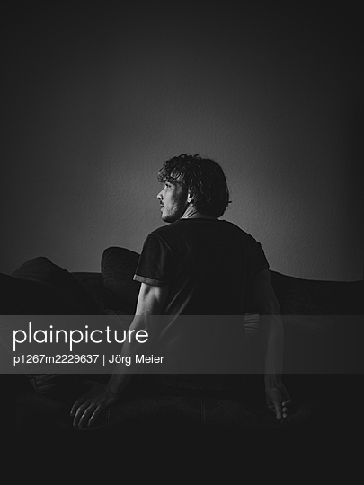 Rückansicht, Junger Mann auf dem Sofa - p1267m2229637 von Jörg Meier