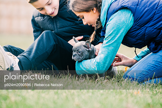 Children playing with puppy on grass - p924m2090596 by Rebecca Nelson