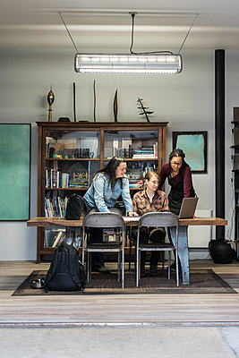 Three women gathered around table in office area of a metal workshop. - p1100m1544188 by Mint Images