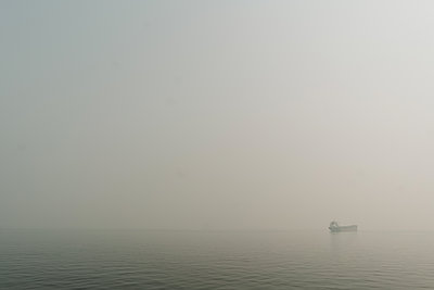 View through wildfire smoke of a freighter ship on Puget Sound - p1166m2212327 by Cavan Images
