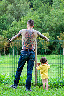 Back view of a tattooed man with his little son standing in front of a fence - p300m1068860f by Xose Casal