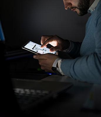 Businessman working on tablet in office at night - p300m1581204 von Uwe Umstätter