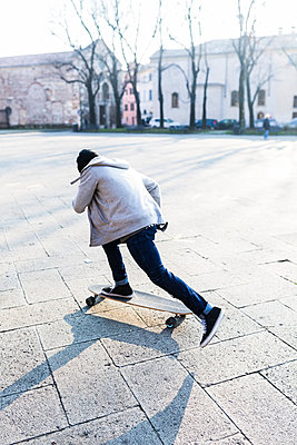 Young man skateboarding on an urban squarre - p300m2024012 von Giorgio Fochesato