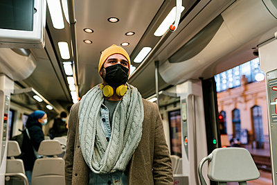 Man wearing protective face mask looking away while standing in train - p300m2251751 by Ezequiel Giménez