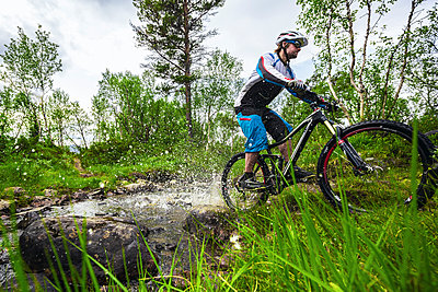 Mountain biker passes through a small creek in Valadalen, Sweden. - p343m1090334 by Elias Kunosson