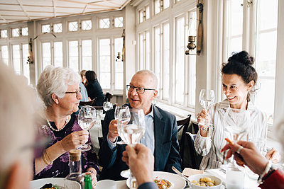 Senior friends with wineglass toasting in restaurant - p426m2149140 by Maskot