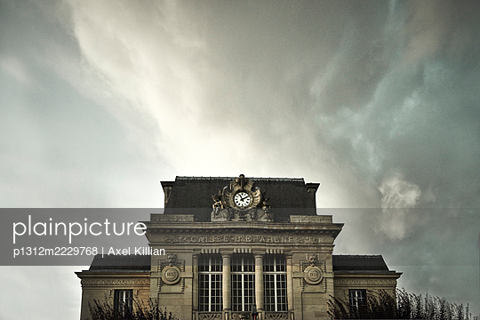 France, Manor house with clock in front of sky with thunderstorm atmosphere - p1312m2229768 by Axel Killian
