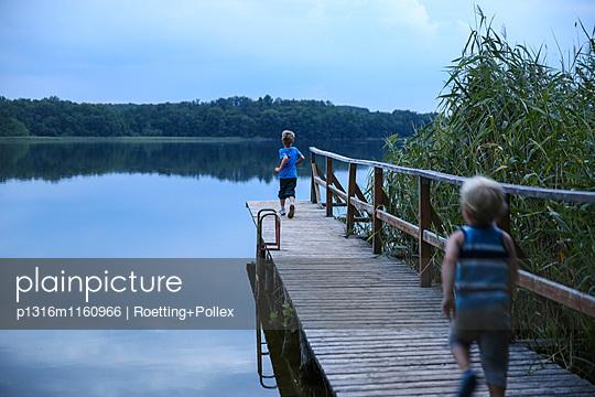 Zwei Jungen laufen über einen Steg an einem See, Biosphärenreservat Schorfheide-Chorin, Neudorf, Friedenfelde, Uckermark, Brandenburg, Deutschland - p1316m1160966 von Roetting+Pollex