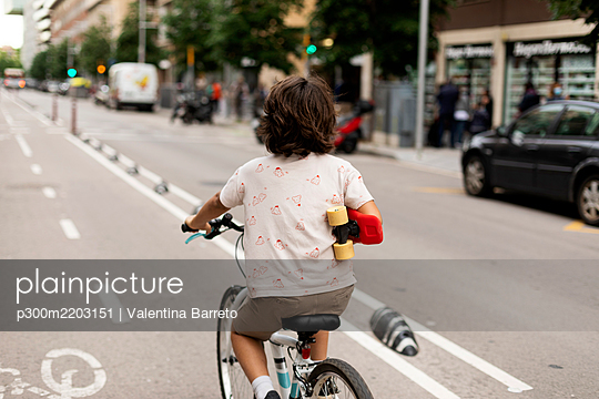 Boy holding skateboard while riding bicycle on street - p300m2203151 by Valentina Barreto