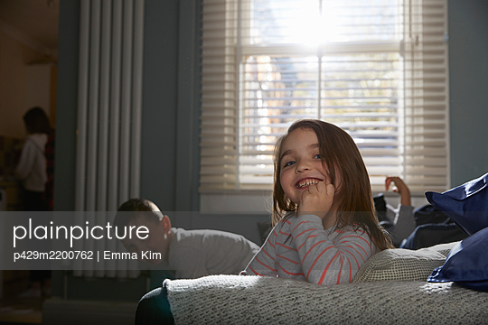Two children sitting on a sofa in their pajamas, smiling at camera. - p429m2200762 by Emma Kim