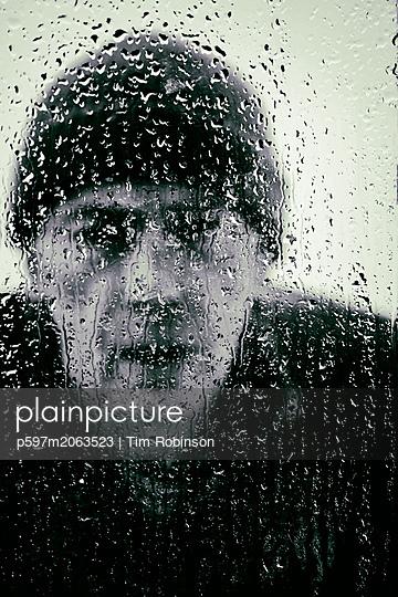 Man looking through rain splattered window - p597m2063523 by Tim Robinson