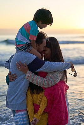 Affectionate family hugging on ocean beach at sunset - p1023m2200918 by Trevor Adeline